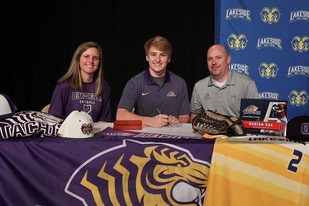 Downtown Andrew Cox is joined by his mother Betsy, left, and father Robbie Friday after signing a letter of intent to play baseball at Ouachita Baptist University.  - Photo by Richard Rasmussen from The Sentinel-Record