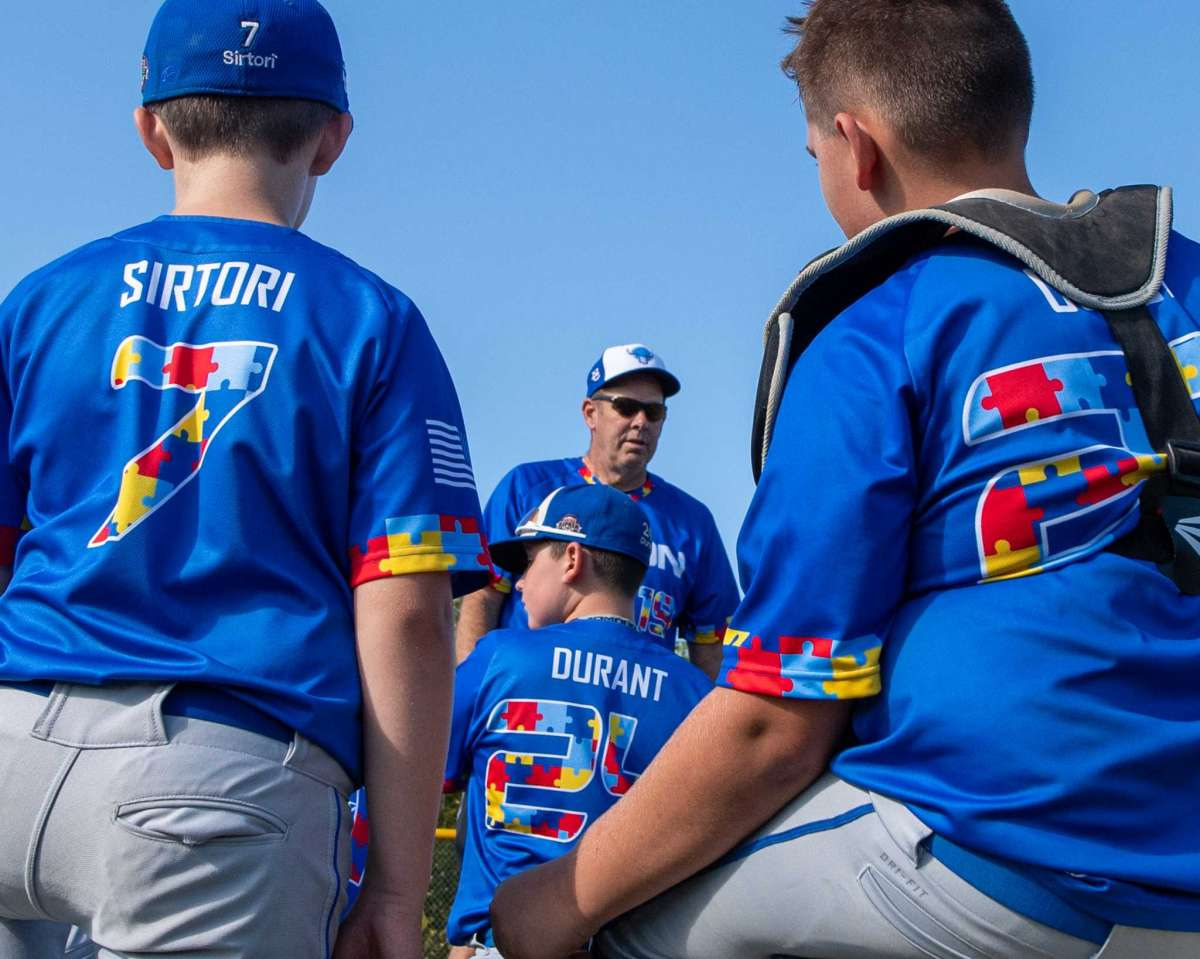 North Colonie Bison 11U coach Sean Gavin talks to his team prior to a game against Guilderland at the Boght Road Baseball complex in Colonie, NY, on Saturday, Sept. 26. The coaches and players were all sporting jerseys with colored puzzle pieces, the symbol for autism, fashioning their numbers and trim (Jim Franco/special to the Times Union.)