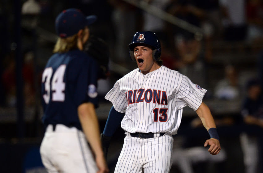 June 11, 2021;  Tucson, Arizona, USA;  Arizona Wildcats outfielder Tyler Casagrande (13) reacts as he scores a run ahead of Ole Miss Rebels musty Tyler Myers (34) during the eighth round of the NCAA Baseball Tucson Super Regional at Hi Corbett Field.  Mandatory Credit: Joe Camporeale-USA TODAY Sports