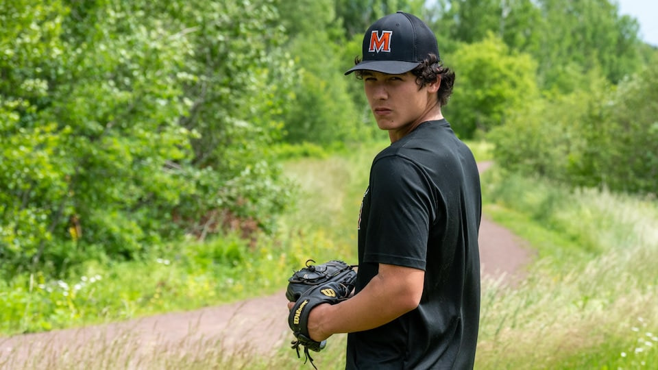 Young man with team hat and baseball glove.  He waits before throwing a ball.